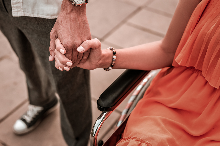 couple holding hands wheelchair