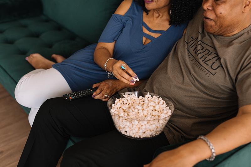 couple se blottissant sur le canapé regardant netflix et mangeant du pop-corn