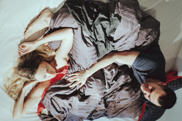 couple in bed engaged in foreplay